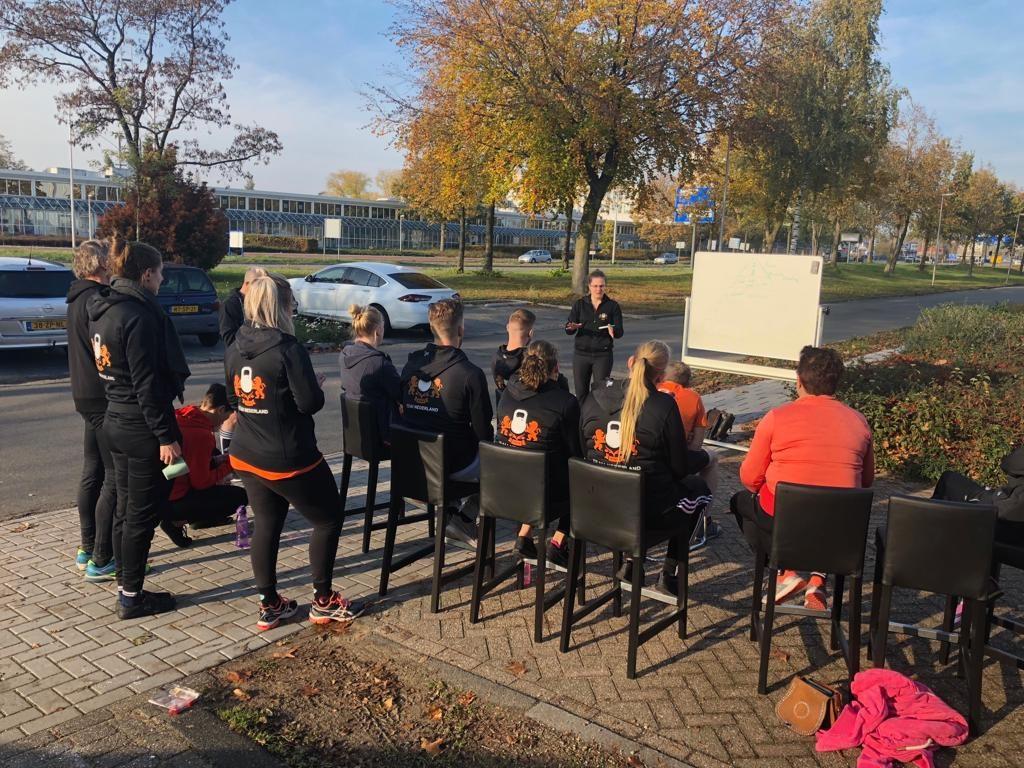 Bondscoach Naomi Kooiker legt de atleten uit hoe ze zich mentaal kunnen voorbereiden op hun set.
